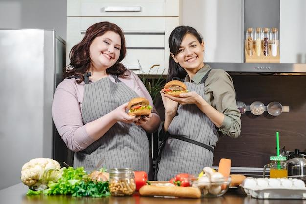 Twee gelukkige jonge vrouwen in schorten die heerlijke hamburgers in hun handen houden en naar de camera in de keuken kijken