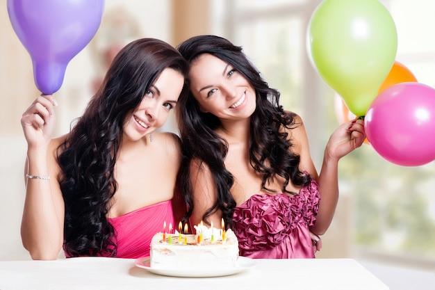 Twee gelukkige jonge vrouwen met cake