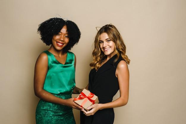 Twee gelukkige jonge vrouwen van verschillende nationaliteiten houden een cadeautje vast