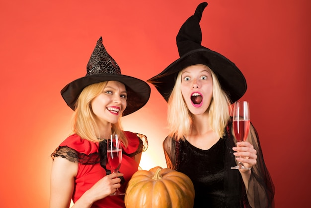Twee gelukkige jonge vrouwenmeisjes in de kostuums van heksenhalloween op partij over oranje muur.