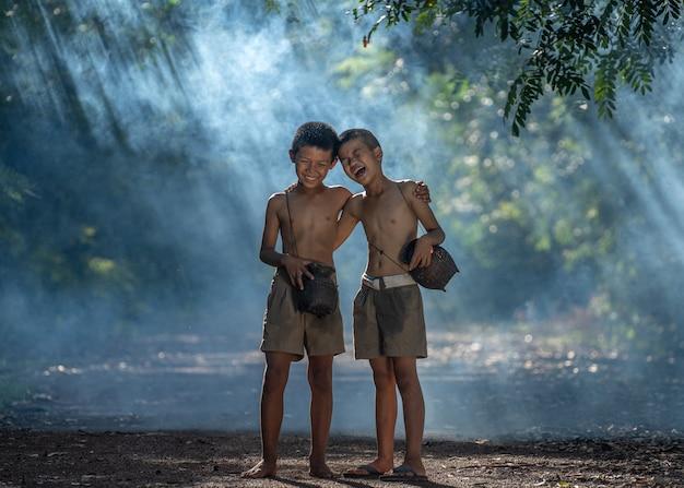 Twee gelukkige jongens en glimlachen bij openlucht, platteland van thailand