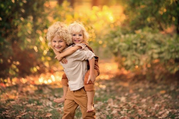 Twee gelukkige jongens spelen in het park in de vroege herfst