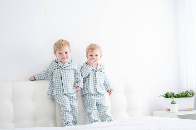 Twee gelukkige jongensbroers op wit bed in pyjama die samen pret hebben