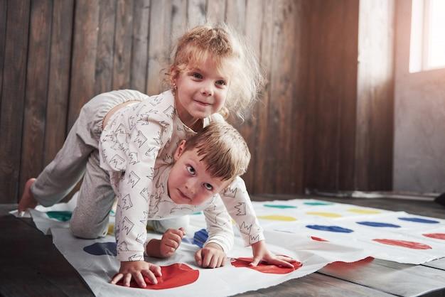 Twee gelukkige kinderen die binnenshuis bij twister spelen. broer en zus hebben een leuke vakantie