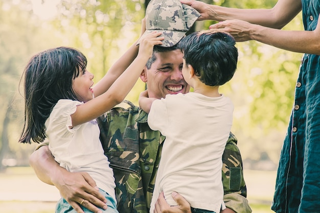 Twee gelukkige kinderen en hun moeder ontmoeten en knuffelen militaire vader in camouflage uniform buitenshuis