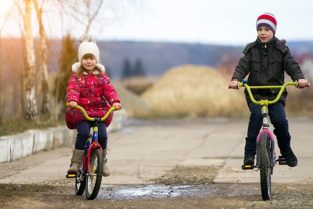 Twee gelukkige kinderen jongen en meisje fietsen buiten bij koud weer