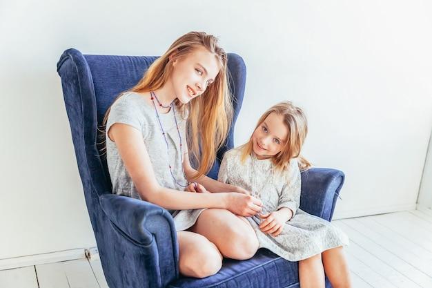 Twee gelukkige kinderen zittend op een gezellige blauwe stoel ontspannen spelen in witte woonkamer binnenshuis. meisje speelt met tienermeisje dat haar liefdeszorg toont. zusters die plezier hebben thuis.