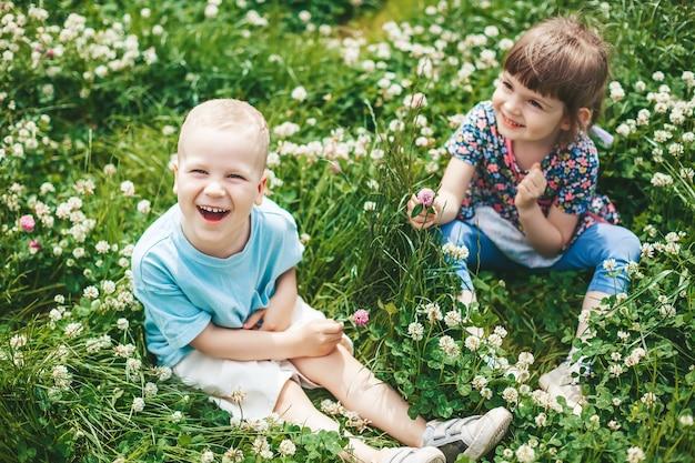 Twee gelukkige kindervrienden, een jongen en een meisje, zittend op een klaverveld, samen plezier maken