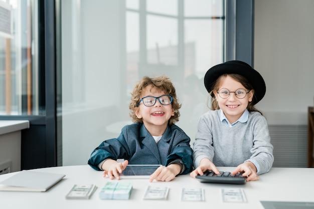 Twee gelukkige kleine accountants met tablet en rekenmachine die naar je kijken terwijl ze geld tellen en je salaris op kantoor geven