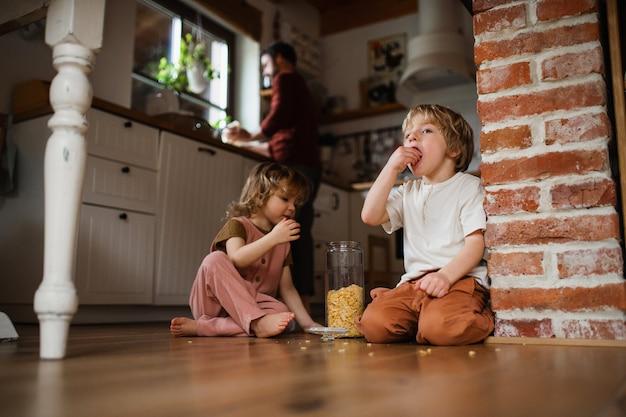 Twee gelukkige kleine kinderen met vader die thuis cornflakes op de vloer eet