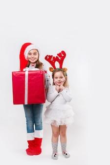 Twee gelukkige kleine lachende kinderen in kerstmuts en herten hoorns met grote kerst cadeau doos en snoep. kersttijd