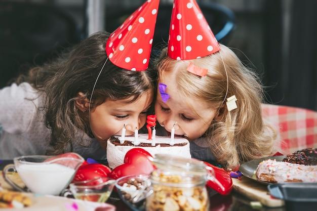 Twee gelukkige kleine meisjes kind een verjaardag vieren met taart aan tafel is mooi en mooi