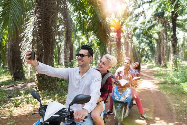 Twee gelukkige koppels op scooters