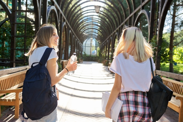 Twee gelukkige lachende pratende meisjes tieners studenten lopen samen, jonge vrouwen met rugzakken, zonnige dag op de achtergrond van het park, achteraanzicht