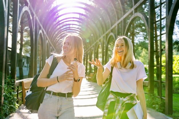 Twee gelukkige lachende pratende meisjes tieners studenten lopen samen, jonge vrouwen met rugzakken, zonnige dag op de achtergrond van het park