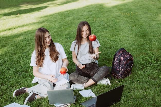 Twee gelukkige lachende vrouwelijke studenten zitten in het park op het gras met boeken en laptops, eten appels, studeren en bereiden zich voor op examens. onderwijs op afstand. zachte selectieve focus.