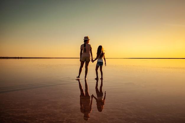 Twee gelukkige lieftallige zussen lopen langs het spiegelzoutmeer en genieten van de vurige zonsondergang