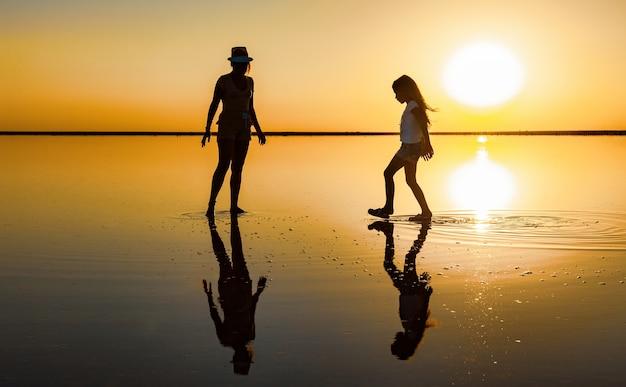 Twee gelukkige lieftallige zusters wandelen langs het spiegelzoutmeer en genieten van de vurige avondzonsondergang