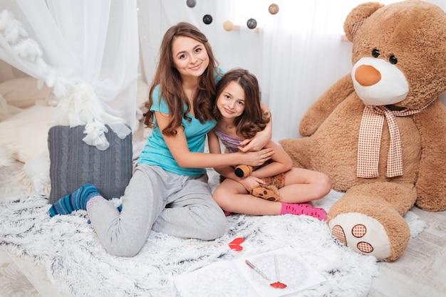 Twee gelukkige lieve zussen zitten en knuffelen in de kinderkamer thuis