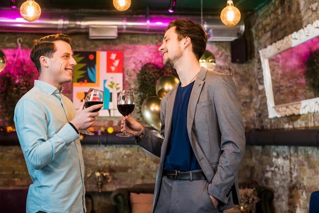 Twee gelukkige mannelijke vrienden met wijn die in partij genieten van