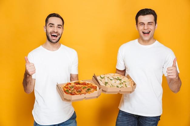 Twee gelukkige mannen vrijgezellen jaren '30 in witte t-shirts die glimlachen en pizzadozen vasthouden terwijl ze geïsoleerd over gele muur staan