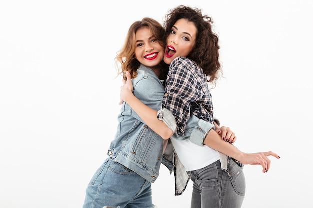 Twee gelukkige meisjes die aan elkaar over witte muur koesteren