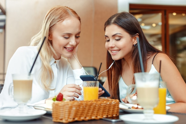Twee gelukkige meisjes die aan muziek met gedeelde oortelefoons samen in aardig koffie drinken. geniet van muziek en entertainment
