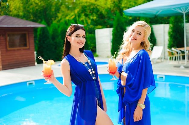 Twee gelukkige meisjes die bij zwembad met cocktails rusten.