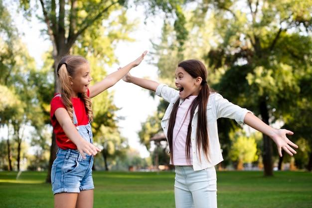 Twee gelukkige meisjes die hun handen uitrekken