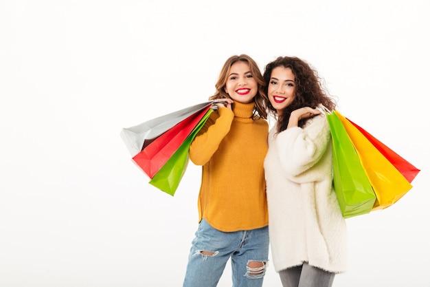Twee gelukkige meisjes die in sweaters met pakketten de camera over witte muur bekijken
