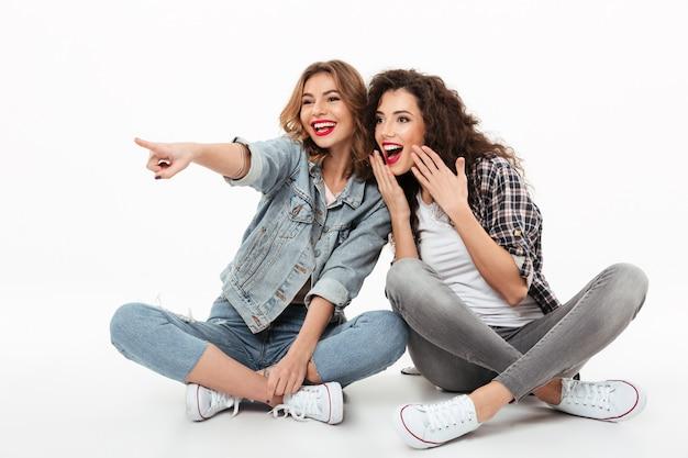 Twee gelukkige meisjes die op de vloer samen zitten en weg over witte muur kijken
