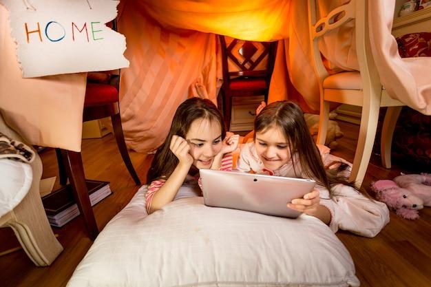 Twee gelukkige meisjes die 's nachts digitale tablet in de slaapkamer gebruiken