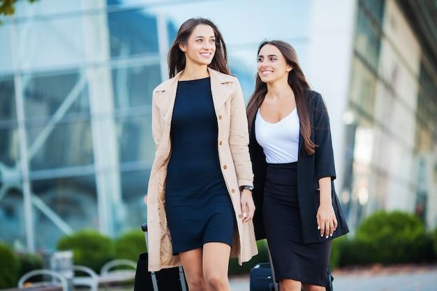 Twee gelukkige meisjes die samen in het buitenland reizen, die kofferbagage op luchthaven dragen