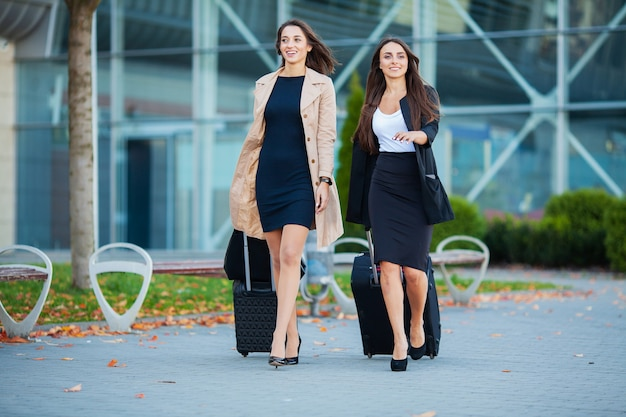 Twee gelukkige meisjes die samen naar het buitenland reizen, die kofferbagage in luchthaven dragen