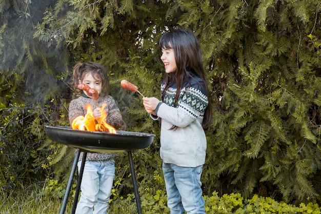 Twee gelukkige meisjes die worsten op draagbare barbecue roosteren