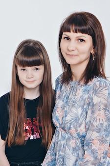 Twee gelukkige meisjes glimlachen. portret van een moeder en dochter omarmen. het concept van familierelaties, vrienden, familiedag, moederdag
