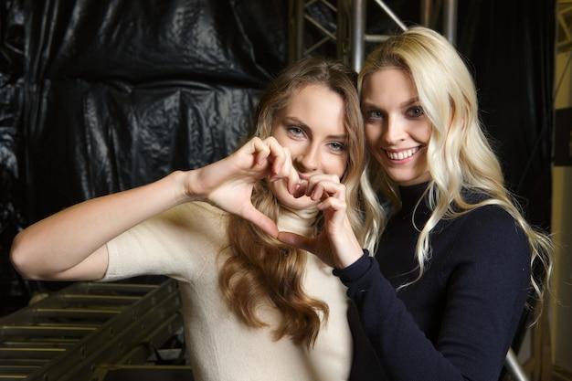 Twee gelukkige meisjes in gebreide kleding bij backstage van manierweek maken hartvorm door haar handen