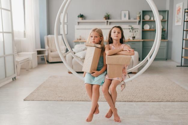 Twee gelukkige meisjes in mooie jurken die op schommeling met giftdozen in hun handen zitten