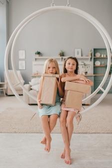 Twee gelukkige meisjes in mooie jurken zittend op schommel met geschenkdozen in hun handen in de kinderkamer