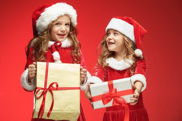 Twee gelukkige meisjes in santa claus hoeden met geschenkdozen op rood