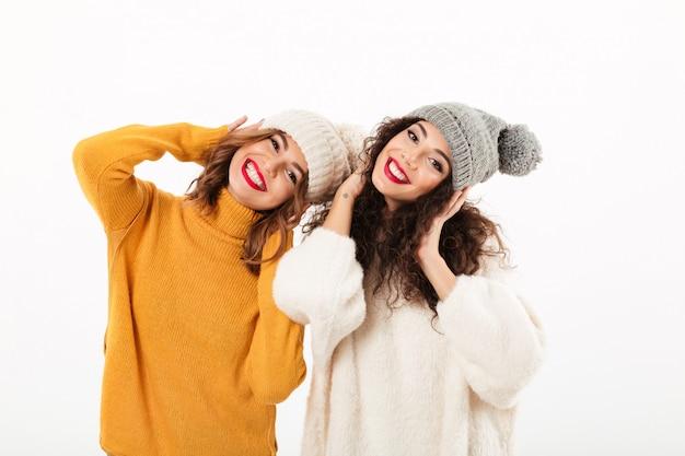 Twee gelukkige meisjes in sweaters en hoeden die pret samen over witte muur hebben