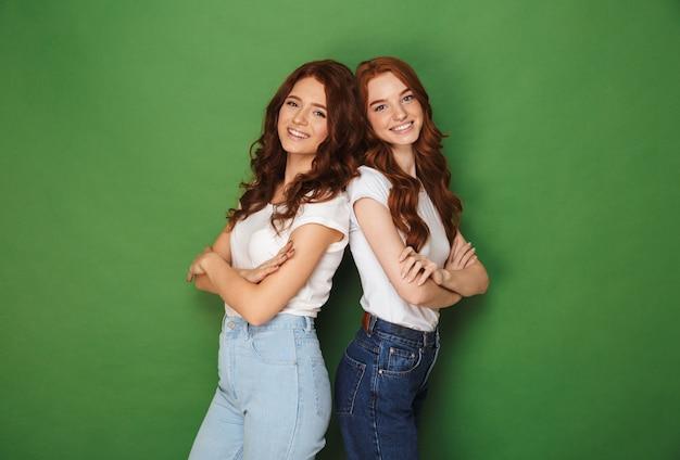 Twee gelukkige meisjes jaren '20 met gember haar in vrijetijdskleding glimlachen naar de camera en staan rug aan rug met gekruiste armen, geïsoleerd op groene achtergrond