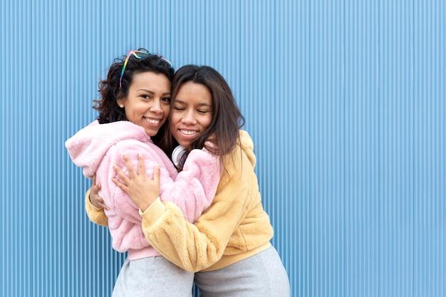 Twee gelukkige meisjes knuffelen elkaar liefdevol