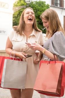 Twee gelukkige meisjes lachen en roddelen met de telefoon na het winkelen mooie vrienden op straat