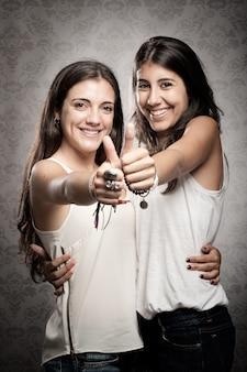 Twee gelukkige meisjes met duimen omhoog