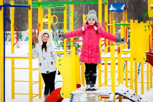 Twee gelukkige meisjes, moeder en dochter spelen op een speelplaats op ijzige winterdag.