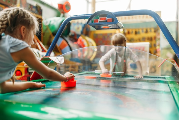 Twee gelukkige meisjes spelen airhockey in game center