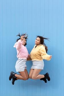 Twee gelukkige meisjes springen op en neer en nemen een foto met hun mobiele telefoon in de lucht