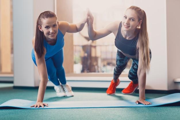 Twee gelukkige meisjes voeren sportenoefening bij training uit