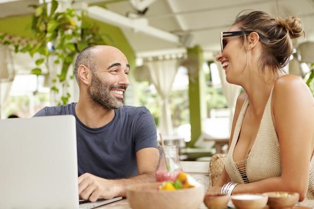 Twee gelukkige mensen met plezier en lachen, zittend op terras tijdens het ontbijt. knappe vrolijke man met stoppels met behulp van laptop pc, glimlachend en praten met stijlvolle vrouw in tinten.